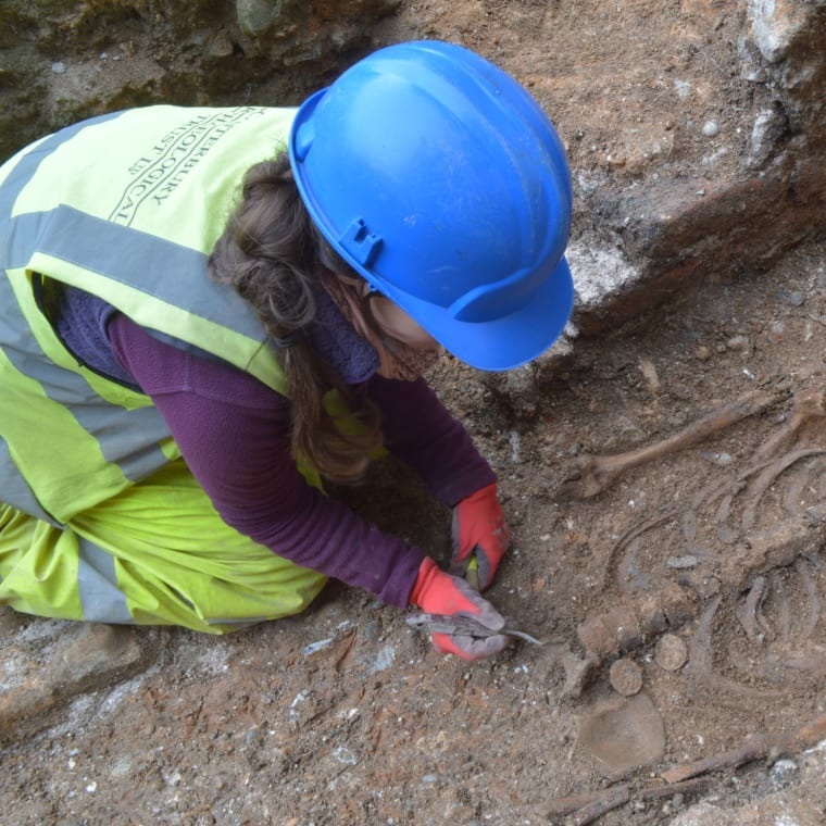 An archaeologist working at the burial site of Abbot John of Wheathampstead